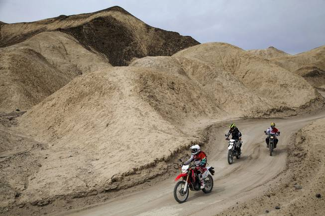 On a Honda CRF250L, Mark Buche, followed by Ty van Hooydonk on a Kawasaki KLX250, followed by a Suzuki DR-Z400S piloted by jun Villegas, the trio rides through Twenty Mule Team Canyon, located in the Furnace Creek area of Death Valley, a one way 2.7 mile loop and the road is unpaved, April 18, 2014.