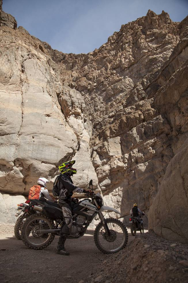 Ty van Hooydonk, stops on his Kawasaki KLX250S to look at the beauty of Titus Canyon Narrow on a recent visit to Death Valley National Park. Jun Villegas, aboard a Suzuki DR-Z400S continues desert journey with Mark Buche, on a Honda CRF250L following.