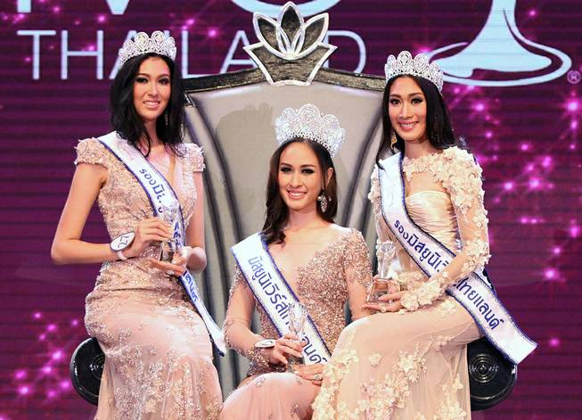 In this photo taken May 17, 2014, Weluree Ditsayabut, center, poses with two runner-ups Pimbongkod Chankaew, left, and Sunnanipa Krissanasuwan, right, after the Miss Universe Thailand beauty pageant competition in Bangkok, Thailand.