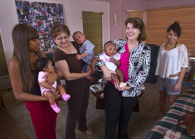 Kathleen Miller, center right, executive director of Living Grace Home, poses with volunteer Caryl Hepker, center left, residents and babies at the home in Henderson Tuesday, June 10, 2014. It is a place for unwed pregnant teenagers, between the ages of 14-22, where they can receive housing, education, and social services. Miller opened Living Grace Home in 2007.