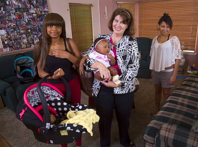 Kathleen Miller, center, executive director of Living Grace Home, poses with residents and babies at the home in Henderson Tuesday, June 10, 2014. It is a place for unwed pregnant teenagers, between the ages of 14-22, where they can receive housing, education, and social services. Miller opened Living Grace Home in 2007.