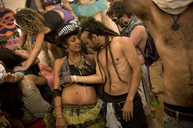 In this photo taken Thursday, June 5, 2014, Israelis dance at a party during Israelis first Midburn festival in the desert near the Israeli kibbutz of Sde Boker.