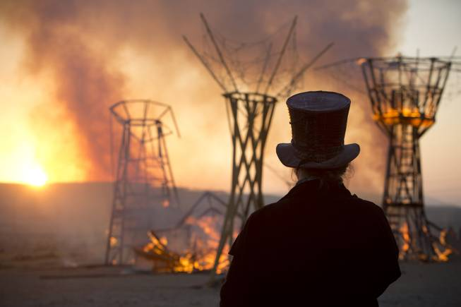 In this Saturday, June 7, 2014, photo, a man looks at a wooden sculpture that was set on fire during Israelis first Midburn Festival in the desert near the Israeli kibbutz of Sde Boker.