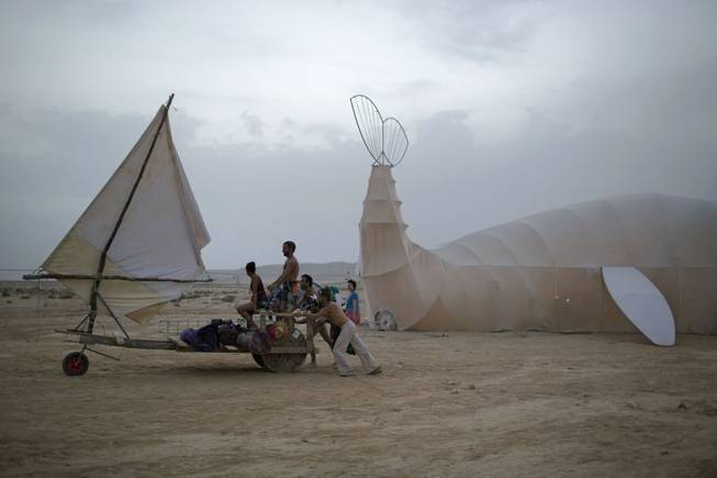 In this photo taken Wednesday, June 4, 2014, Israelis push a sailboat art car at the playa during the Israelis first Midburn festival in the desert near the Israeli kibbutz of Sde Boker.