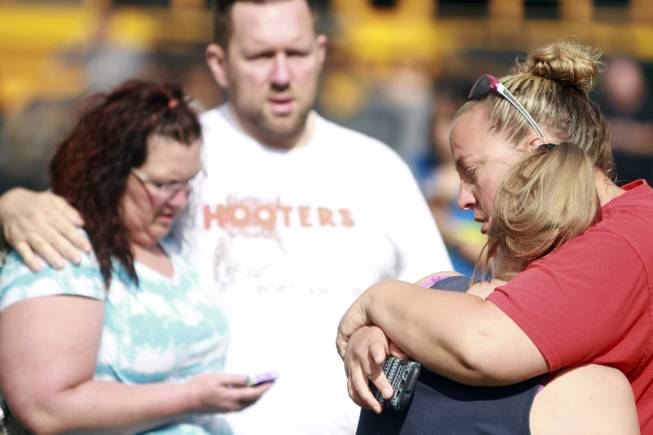 People comfort each other as they await word about the safety of students after a shooting at Reynolds High School Tuesday, June 10, 2014, in Troutdale, Ore. A gunman killed a student at the high school east of Portland Tuesday and the shooter is also dead, police said.