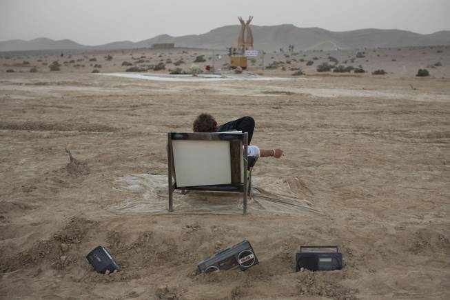 In this photo taken Wednesday, June 4, 2014, an Israeli man rests on a couch during Israelis first Midburn festival in the desert near the Israeli kibbutz of Sde Boker.