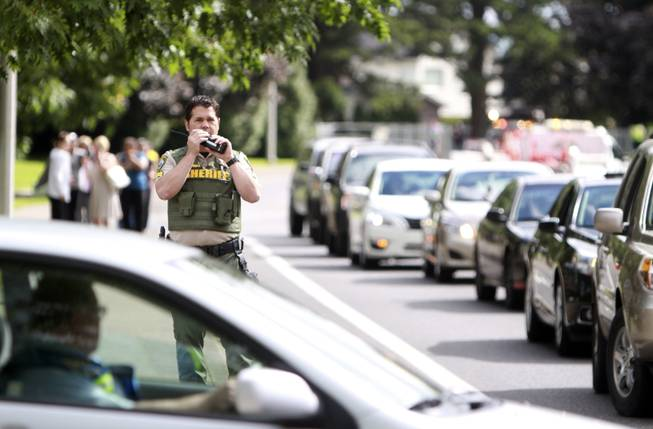 A sheriff's officer speaks in this radio after a shooting at Reynolds High School Tuesday, June 10, 2014, in Troutdale, Ore. A gunman killed a student at the high school east of Portland Tuesday and the shooter is also dead, police said.
