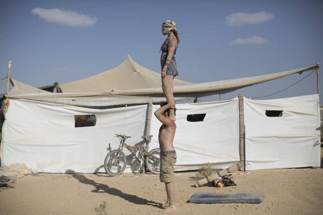 In this photo taken Friday, June 6, 2014, Israeli acrobats perform during Israelis first Midburn festival in the desert near the Israeli kibbutz of Sde Boker.