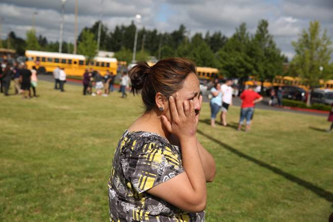A woman waits to hear about the safety of students after a shooting at Reynolds High School Tuesday, June 10, 2014, in Troutdale, Ore. A gunman killed a student at the high school east of Portland Tuesday and the shooter is also dead, police said.