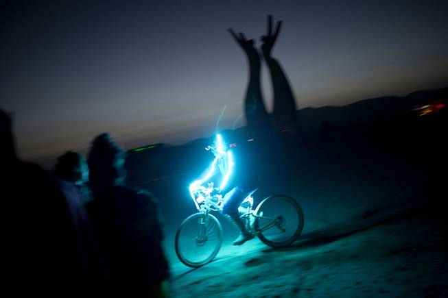 In this photo taken Thursday, June 5, 2014, an Israeli man rides a bicycle as the sun goes down during Israelis first Midburn festival in the desert near the Israeli kibbutz of Sde Boker.