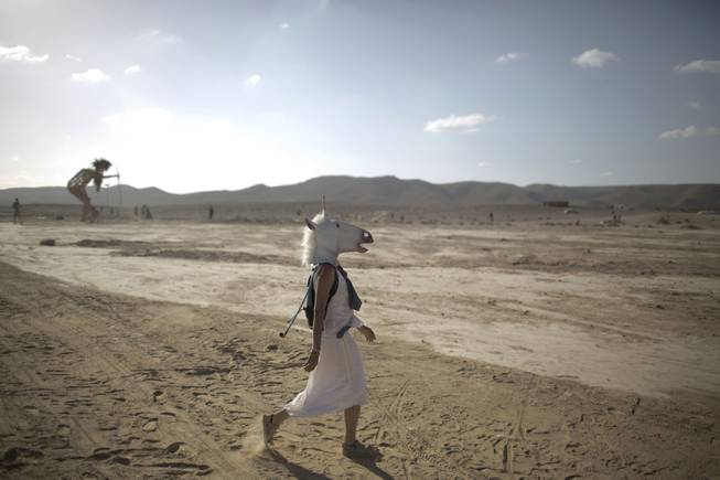 In this photo taken Friday, June 6, 2014, An Israeli woman wears a unicorn mask as she walks in the playa during Israelis first Midburn festival in the desert near the Israeli kibbutz of Sde Boker.