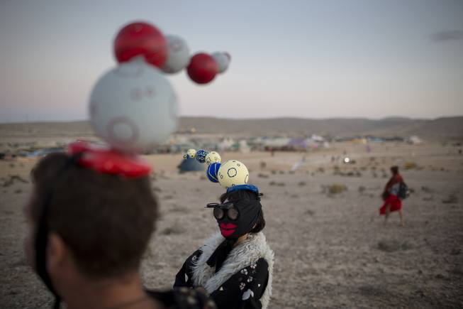 In this photo taken Friday, June 6, 2014, Israelis in costumes walk around the playa during Israelis first Midburn festival in the desert near the Israeli kibbutz of Sde Boker.