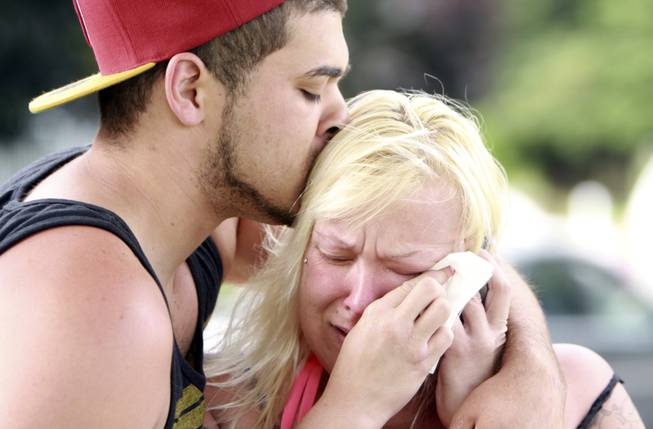 Two people comfort each other as they await word about the safety of students after a shooting at Reynolds High School Tuesday, June 10, 2014, in Troutdale, Ore. A gunman killed a student at the high school east of Portland Tuesday and the shooter is also dead, police said.
