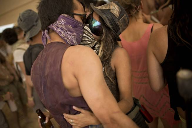 In this photo taken Thursday, June 5, 2014, Israelis kiss at a party during Israelis first Midburn festival in the desert near the Israeli kibbutz of Sde Boker.
