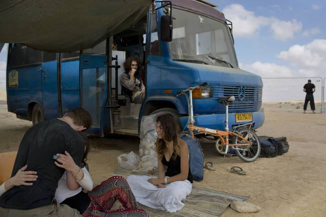 In this photo taken Saturday, June 7, 2014, Israelis sits under the shade during Israelis first Midburn festival in the desert near the Israeli kibbutz of Sde Boker.