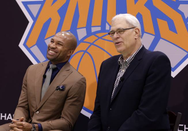 Derek Fisher, left, laughs, while New York Knicks president Phil Jackson speaks during a news conference in Tarrytown, N.Y., Tuesday, June 10, 2014. The Knicks hired Fisher as their new coach on Tuesday, with Jackson turning to one of his trustiest former players.