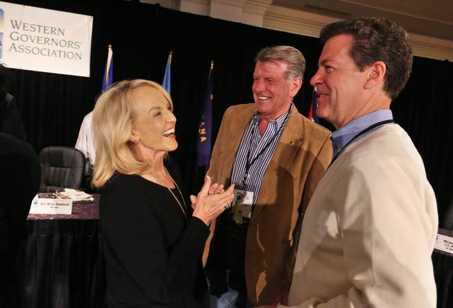 Arizona Gov. Jan Brewer, left, talks with fellow Govs. Sam Brownback of Kansas, right, and Butch Otter of Idaho, during the annual Western Governors' Association Meeting, at the Broadmoor Hotel in Colorado Springs, Tuesday, June 10, 2014. Ten governors from western states attended the second day of the conference Tuesday, discussing common regional issues.