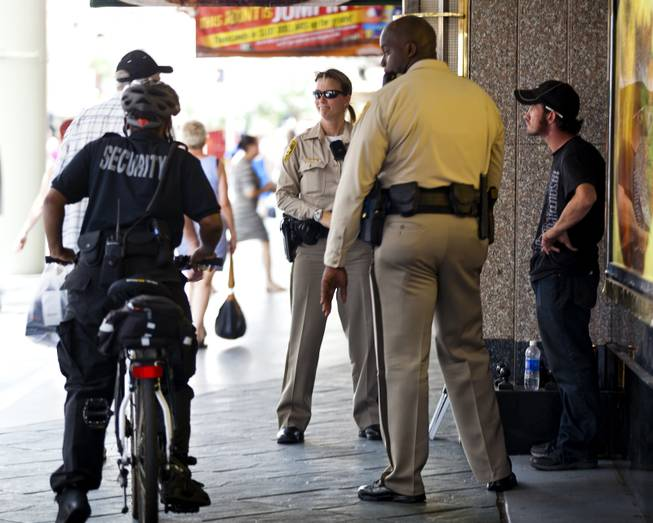 Metro Police officers S. Rumery and A. Reeder stop and talk for a moment while on foot patrol at the Fremont Street Experience.