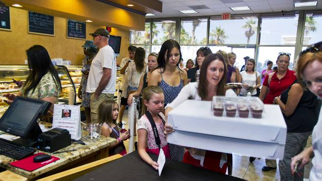 Some customers purchase their pre-ordered cupcakes as others wait patiently in line at Freed's Bakery of Las Vegas to donate and purchase some 35,000 cupcakes for $1 each on Wednesday, June 11, 2014.  The proceeds will be going to aid the families of slain Metro Police officers Metro officers Alyn Beck and Igor Soldo.
