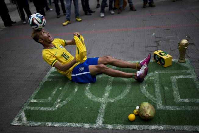 A street performer dressed as a Brazilian national soccer team player, balances a ball on his head during his presentation in downtown Sao Paulo, Brazil, Tuesday, June 10, 2014. The 2014 World Cup is set to begin Thursday, with Brazil and Croatia competing in the opening match in Sao Paulo.