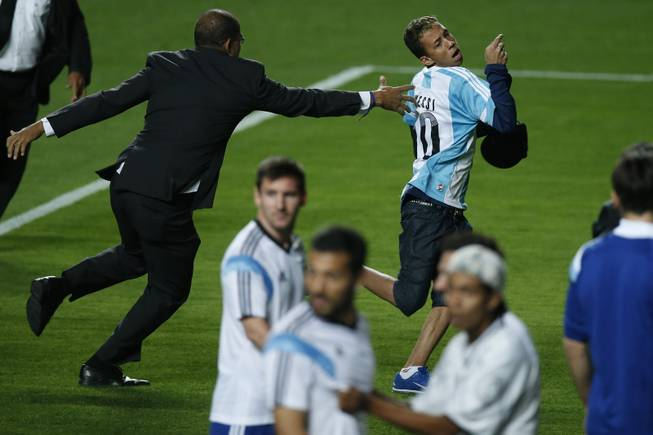 A security guard fails to stop a fan who invaded the pitch wearing an Argentine jersey, top, as Argentina's Lionel Messi, center, and other players look on at the end of a training session at Independencia Stadium in Belo Horizonte, Brazil, Wednesday, June 11, 2014. Argentina will play in group F of the Brazil 2014 soccer World Cup.
