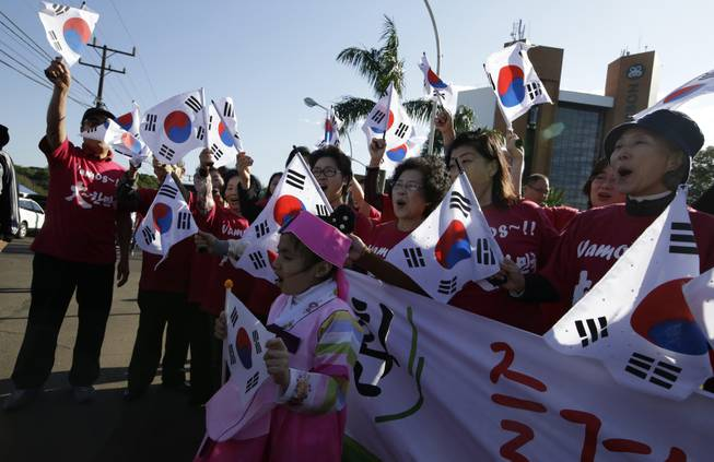 South Korean soccer fans wave their national flags as they wait for the national soccer team's arrival at the team hotel in Foz do Iguacu, Brazil, Wednesday, June 11, 2014. South Korea play in group H of the 2014 soccer World Cup.