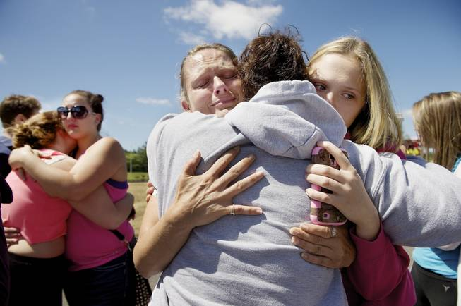 Brandi Wilson, left, and her daughter, Trisha Wilson, 15, right, embrace Trish Hall, a mother waiting for her student, as students arrived at the Fred Meyer grocery store parking lot in Wood Village, Ore., after a shooting at Reynolds High School Tuesday, June 10, 2014, in nearby Troutdale.