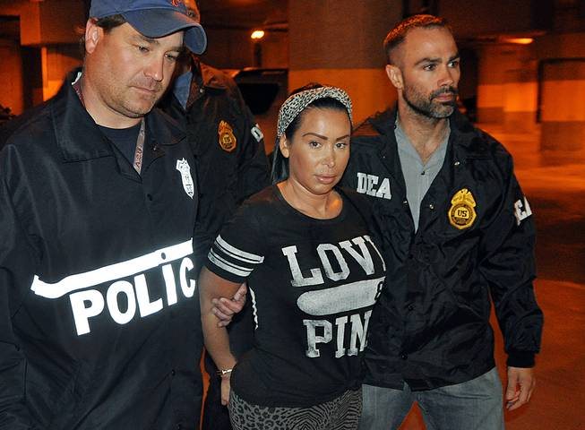 Samantha Barbash, center, is escorted by law enforcement officers following her arrest in New York, Monday, June 9, 2014. Barbash is allegedly part of a crew of New York City strippers who scammed wealthy men.