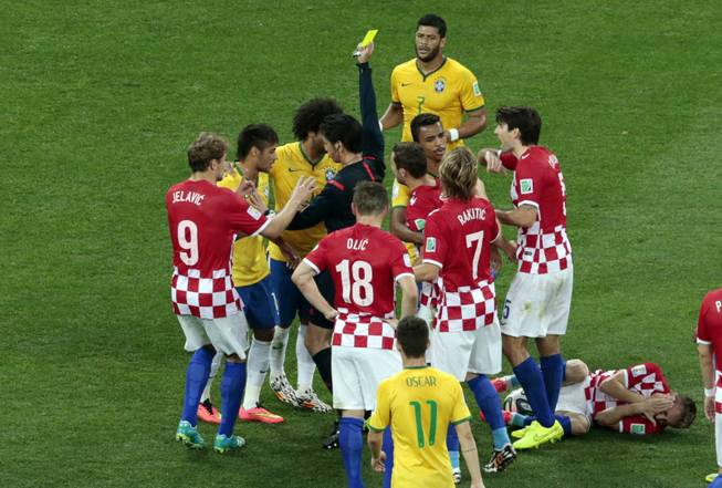 Brazil's Neymar, second left, is booked by referee Yuichi Nishimura from Japan after fouling Croatia's Luka Modric, right, during the group A World Cup soccer match between Brazil and Croatia, the opening game of the tournament, in the Itaquerao Stadium in Sao Paulo, Brazil, Thursday, June 12, 2014.