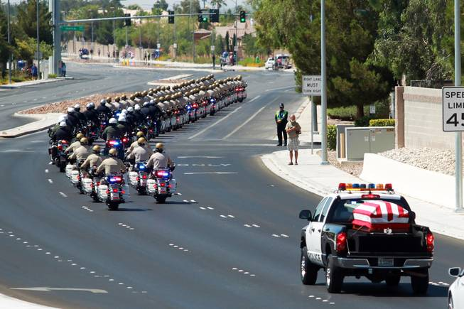 Law enforcement officers lead a Metro truck carrying the body of officer Igor Soldo to Canyon Ridge Church for Thursday, June 12, 2014.
