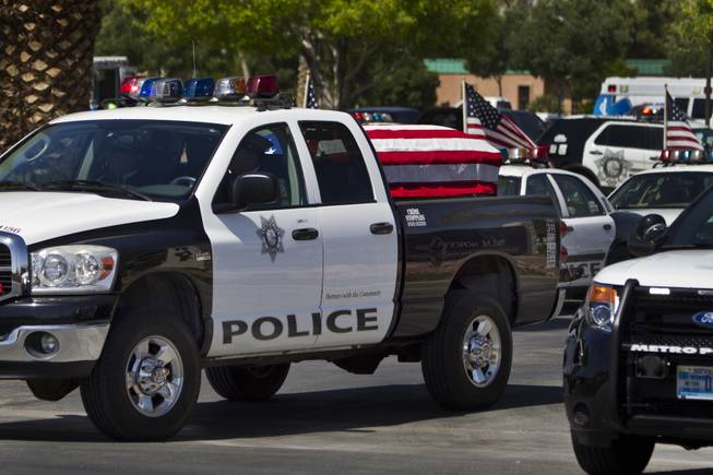 The flag-draped coffin of slain Metro Officer Igor Soldo departs from the Palm Mortuary to the Canyon Ridge Church service on Thursday, June 12, 2014.