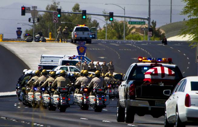 Metro Police Motorcycle Officers and other department officers lead a funeral procession and flag-draped coffin for slain Metro Officer Igor Soldo as it departs from the Palm Mortuary to the Canyon Ridge Church service on Thursday, June 12, 2014.