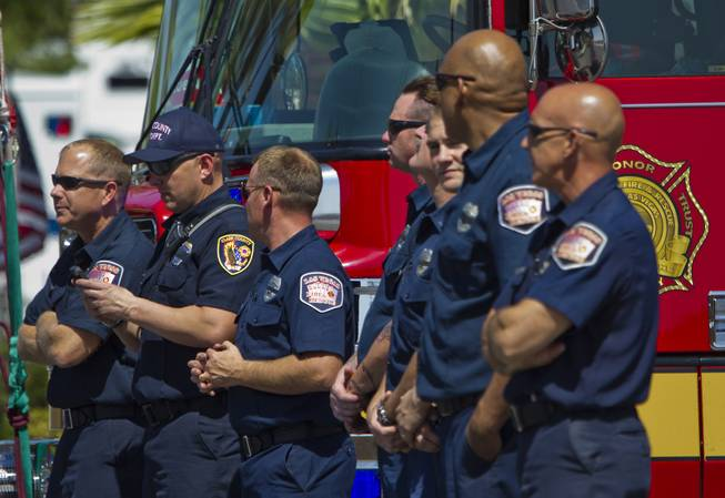 Clark County Firefighters look on as the flag-draped coffin of slain Metro Officer Igor Soldoand procession depart from the Palm Mortuary to the Canyon Ridge Church service on Thursday, June 12, 2014.