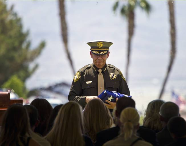 Clark County Sheriff Doug Gillespie carries a folded American flag over to Andrea Soldo, wife of slain Metro Officer Igor Soldo, during funeral services at Palm Mortuary on Thursday, June 12, 2014.