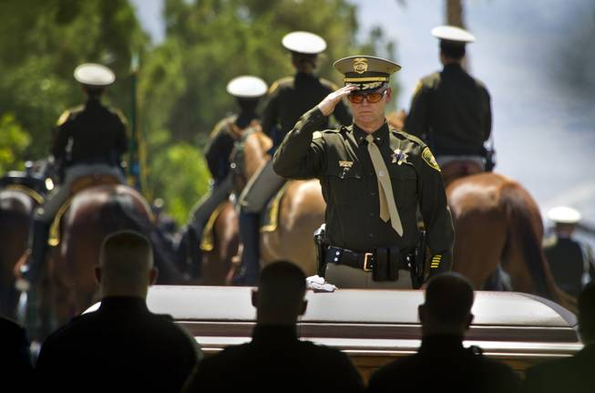 The casket of slain Metro Officer Igor Soldo is saluted by officer after officer ending funeral services at the Palm Mortuary on Thursday, June 12, 2014.