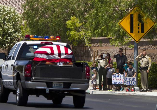 The body of slain Metro Officer Igor Soldo drives past saluting officers and others gathered en route to the Palm Mortuary for funeral services on Thursday, June 12, 2014.