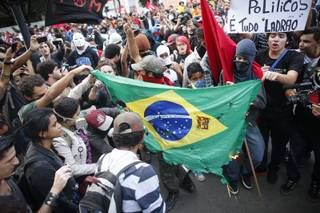 Demonstrators burn a Brazilian flag during a protest against the 2014 World Cup in Belo Horizonte, Brazil, Thursday, June, 12, 2014. The sign in the upper right reads in Portuguese