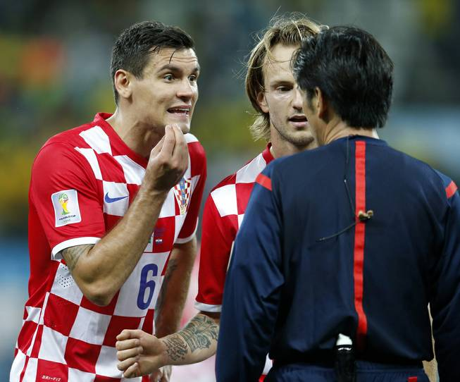 Croatia's Dejan Lovren, left, and teammate Ivan Rakitic, center, complain to referee Yuichi Nishimura, from Japan, after Nishimura issued a penalty against Croatia during the group A World Cup soccer match between Brazil and Croatia in the opening game of the tournament at Itaquerao Stadium in Sao Paulo, Brazil, Thursday, June 12, 2014.