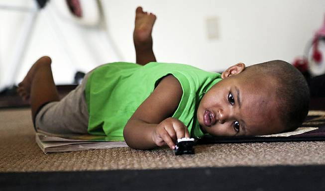 Musa Dayib, 16 months, plays with a toy car at his home Wednesday, June 11, 2014 in Minneapolis. Musa survived an 11-story fall from his home in a Minneapolis high-rise a month ago.