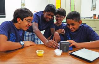 Hyde Park Middle School seventh graders (l-r) Moulin Patel, 13; Ashish Kalakuntla, 12; Anik Patel, 12; and Vidhu Ramakrishnan, 12; look over their invention, which neutralizes pollen, on Tuesday, June 10, 2014. The students will represent Nevada in the national eCybermission competition on June 20.