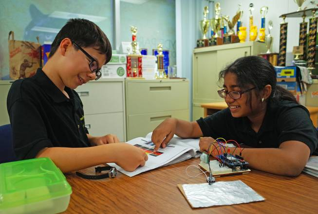 Hyde Park Middle School sixth-graders Craig Hammond, 11, and Pranathi Tallapragada, 11, look over their invention, which alerts parents to children left in unattended cars. The students will represent Nevada in the national eCybermission competition June 20.