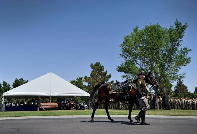 Las Vegas police officer Dallas Reed leads a riderless horse during funeral services for Las Vegas police officer Igor Soldo at Palm Northwest Mortuary & Cemetery on Thursday, June 12, 2014 in Las Vegas. Soldo, 31, and fellow officer, Alyn Beck, 41, were gun down by two assailants at a Cici's Pizza during their lunch break Sunday. Services for Beck are scheduled for Saturday.