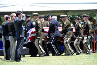 Police honor guard members carry the casket of Las Vegas police officer Igor Soldo for his funeral at Palm Northwest Mortuary & Cemetery on Thursday, June 12, 2014 in Las Vegas. Soldo, 31, and fellow officer, Alyn Beck, 41, were gun down by two assailants at a Cici's Pizza during their lunch break Sunday. Services for Beck are scheduled for Saturday.
