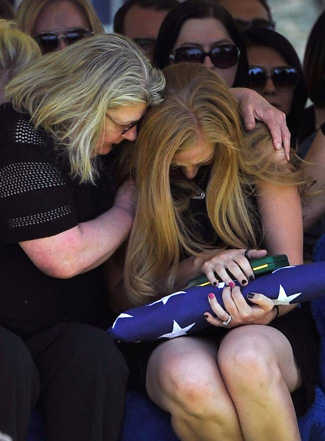 Andrea Soldo is consoled by a family member after receiving a flag during the funeral services for her husband and Las Vegas police officer Igor Soldo at Palm Northwest Mortuary & Cemetery on Thursday, June 12, 2014 in Las Vegas. Soldo, 31, and fellow officer, Alyn Beck, 41, were gun down by two assailants at a Cici's Pizza during their lunch break Sunday. Services for Beck are scheduled for Saturday.