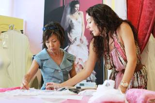 Yuki Moyers and Mina Olive bridal boutique owner Megan Thompson discuss a dress design Saturday, June 7, 2014.