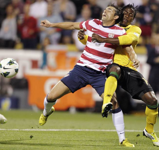United States' Herculez Gomez, left, and Jamaica's Lovel Palmer fight for a loose ball during the first half of a World Cup qualifying soccer match, Tuesday, Sept. 11, 2012, in Columbus, Ohio.