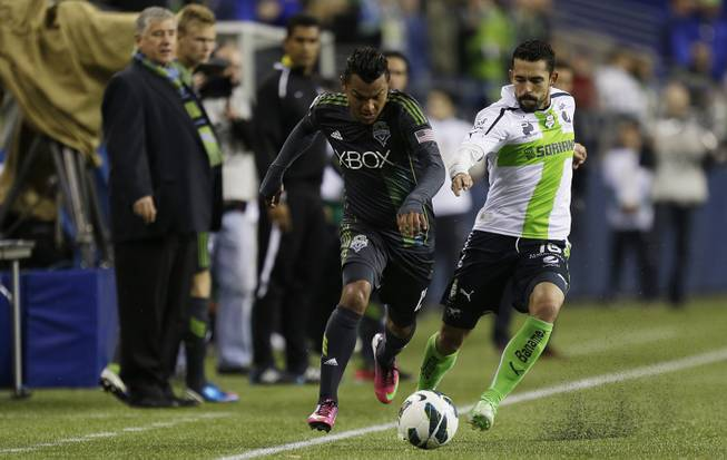 Santos Laguna's Herculez Gomez, right, battles for the ball with Seattle Sounders' Mario Martinez, left, down the sideline in the second half of a CONCACAF semifinal soccer match, Tuesday, April 2, 2013, in Seattle. Gomez had the winning goal as Santos Laguna beat the Sounders 1-0 in the first of two aggregate-score matches.