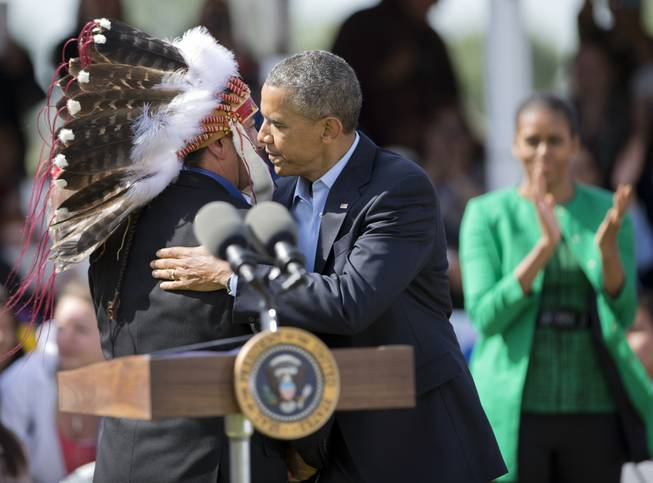 President Barack Obama with first lady Michelle Obama, Standing Rock Sioux Tribal Nation Chairman Dave Archambault II, in Cannon Ball, N.D., Friday, June 13, 2014, during a Cannon Ball flag day celebration, at the Cannon Ball powwow grounds. It's the president's first trip to Indian Country as president and only the third such visit by a sitting president in almost 80 years.