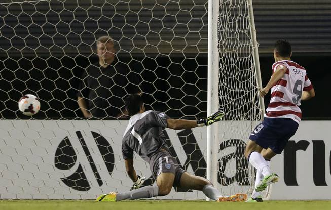The United States' Herculez Gomez, right, scores as Guatemala goalkeeper Ricardo Jerez (1) watches the ball hit the net in the first half during an international friendly soccer match Friday, July 5, 2013, in San Diego.
