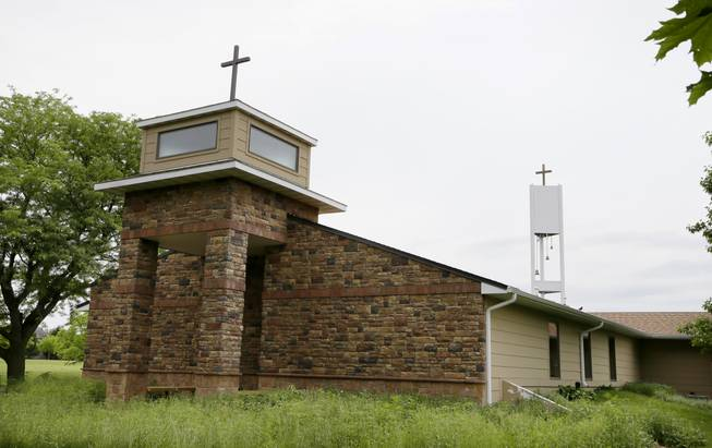 In this June 10, 2014, photo, a cellphone tower inside the bell tower, rear right, is seen over the Resurrection Lutheran Church in Ankeny, Iowa. As wireless companies fill gaps in their networks, many have sought to camouflage the ungainly outdoor equipment that carries the nation's daily diet of calls, text messages and data.